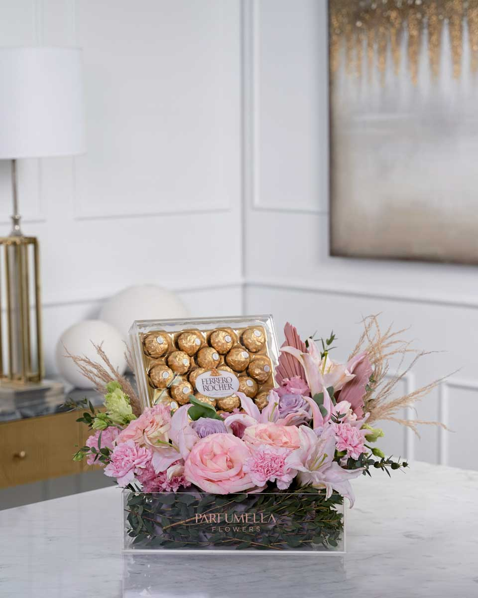 dried palm, roses, lilies, and chocolates on clear box