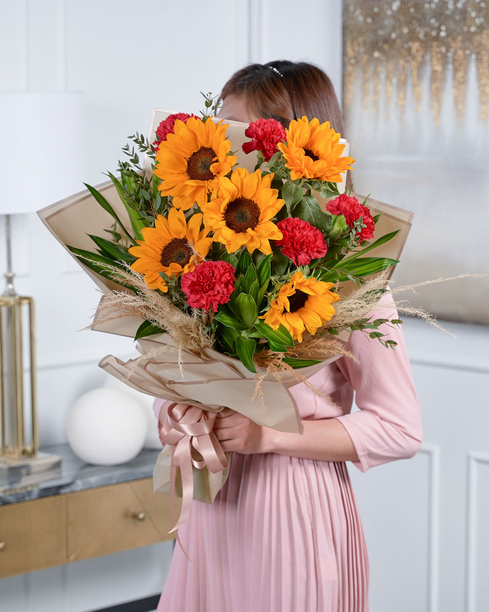 lady holding a bouquet of carnation and sunflowers