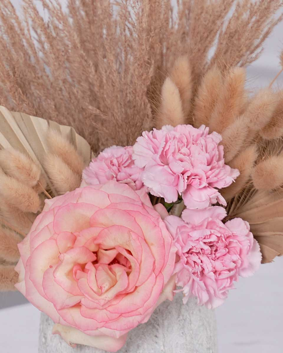 detailed photo of roses and dried blooms on white vase