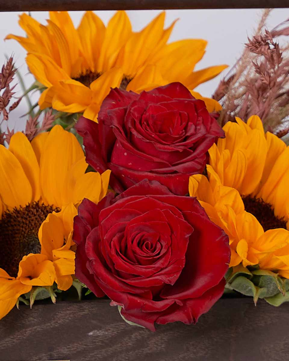 sunflowers, pampas and red roses on wooden box