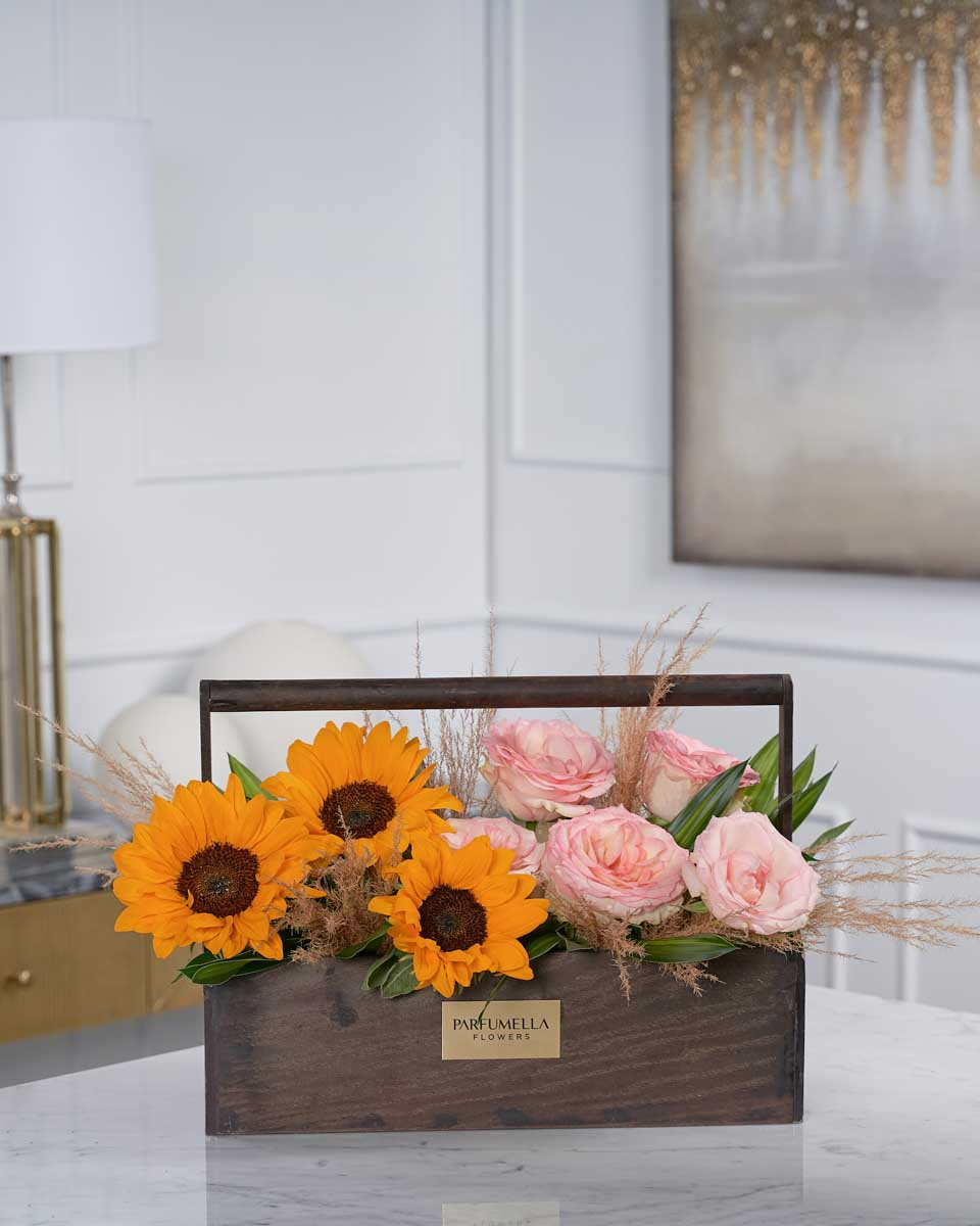 photo of pink roses, sunflower and pampas on wooden basket