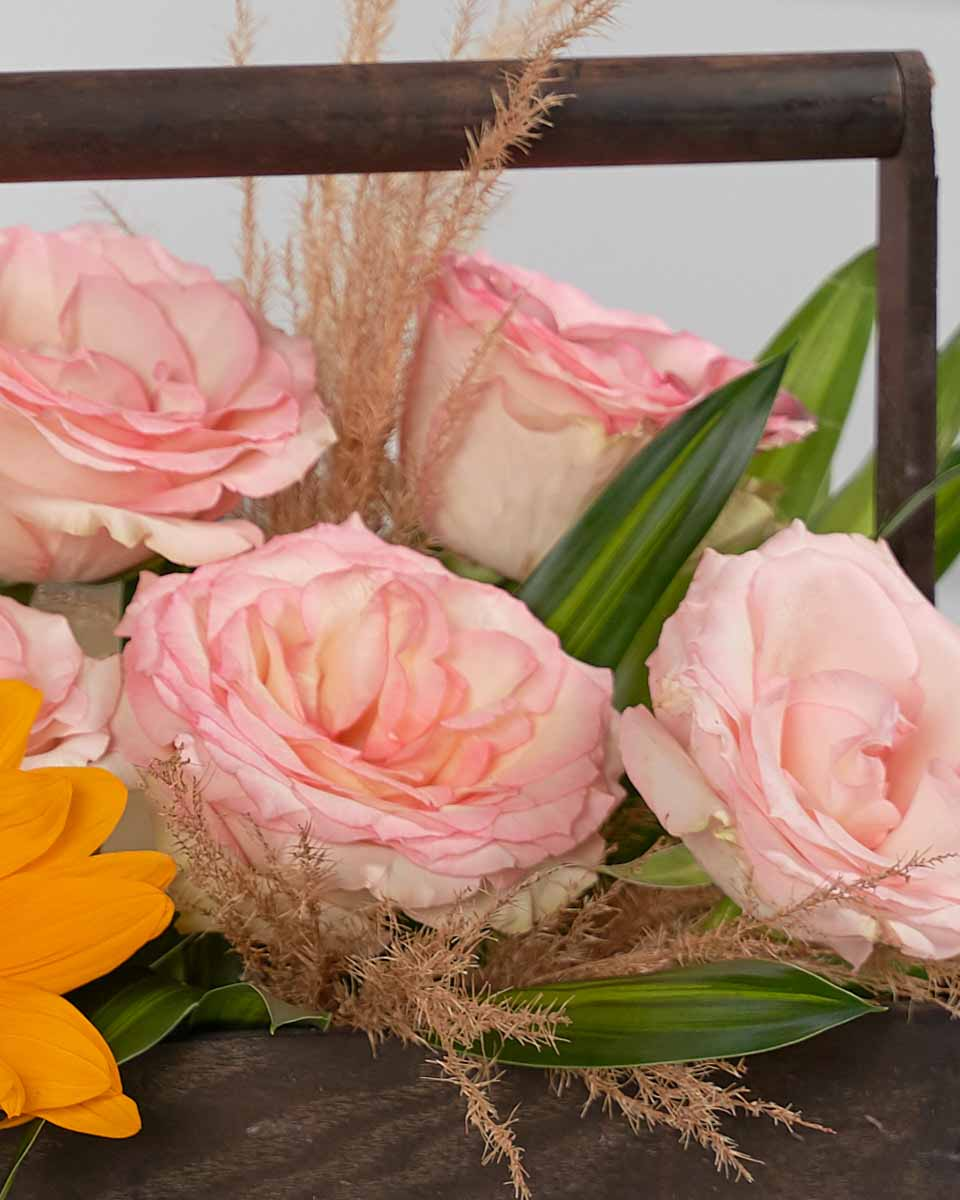 detailed photo of pink roses, sunflower and pampas on wooden basket