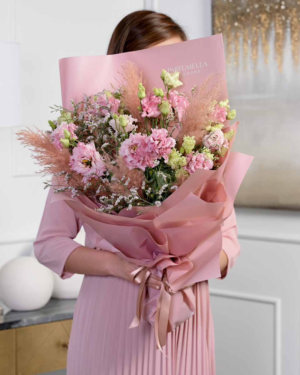lady holding a bouquet of lisianthus, limonium and touch of pampas.