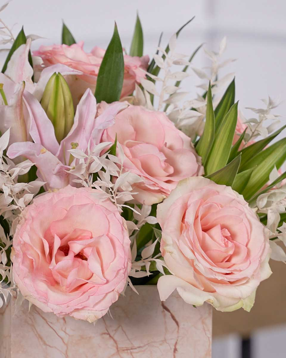 close up photo of roses and lilies on beige box
