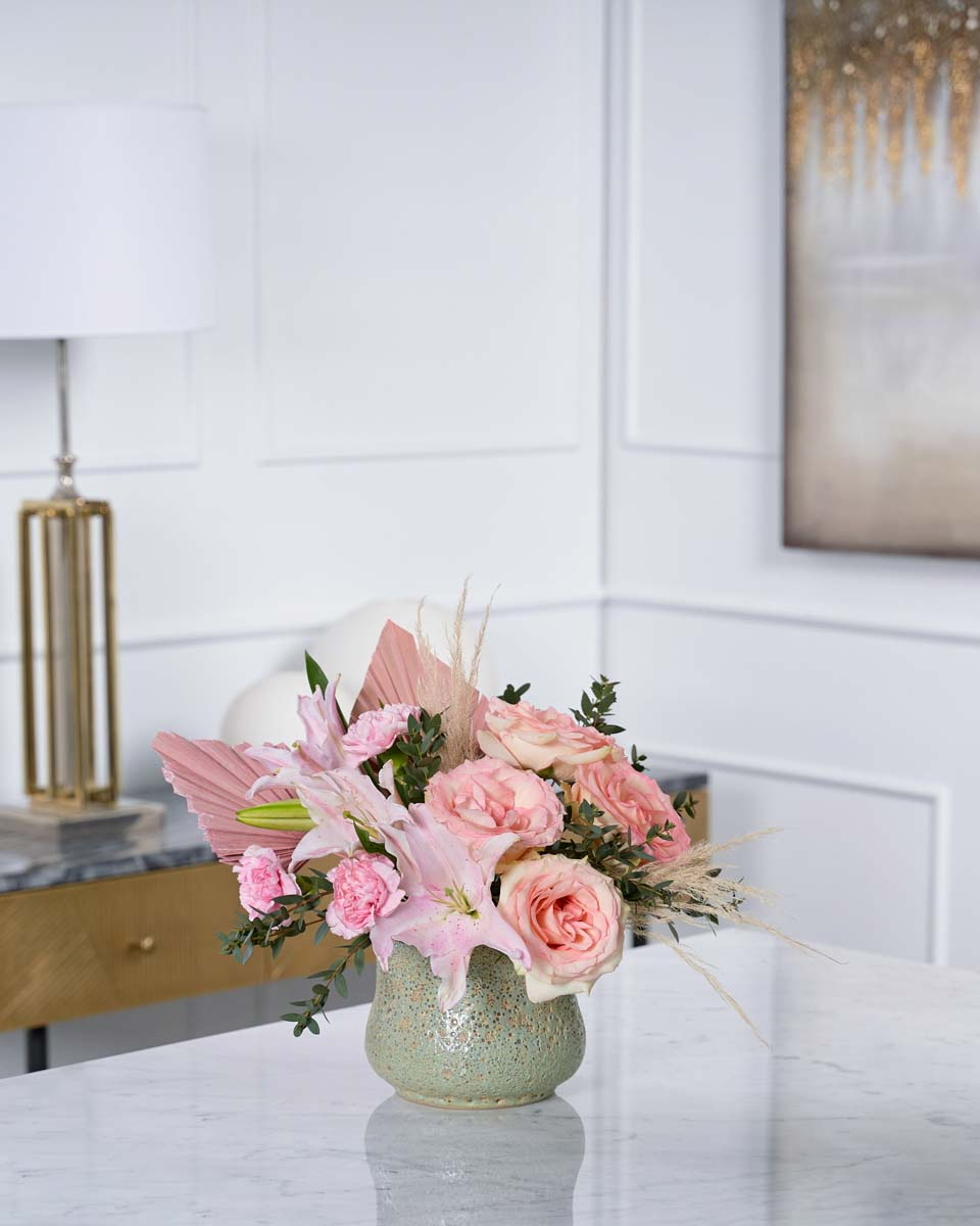 pink roses, lilies and dried palm on green vase