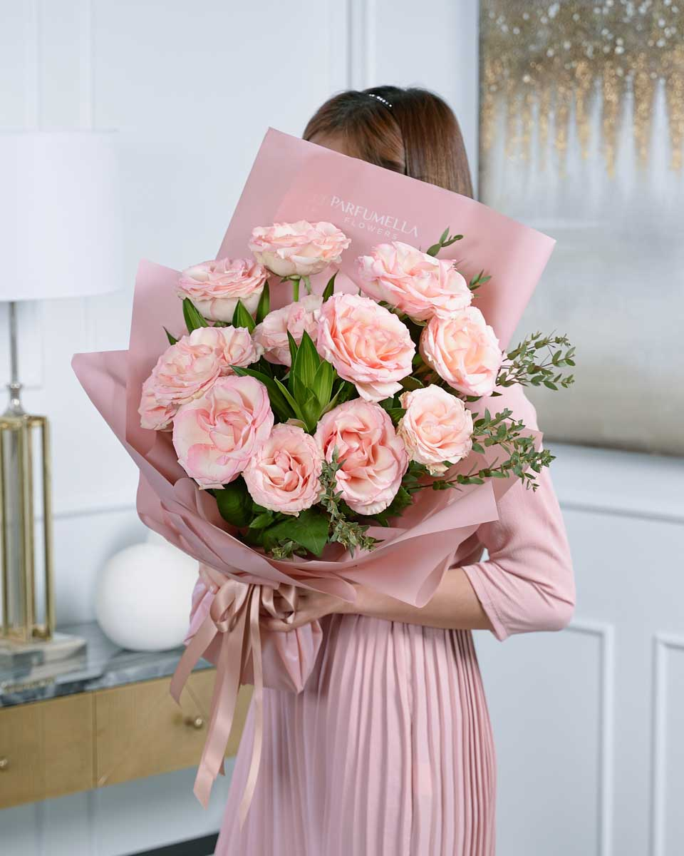 lady holding a bouquet of pink roses