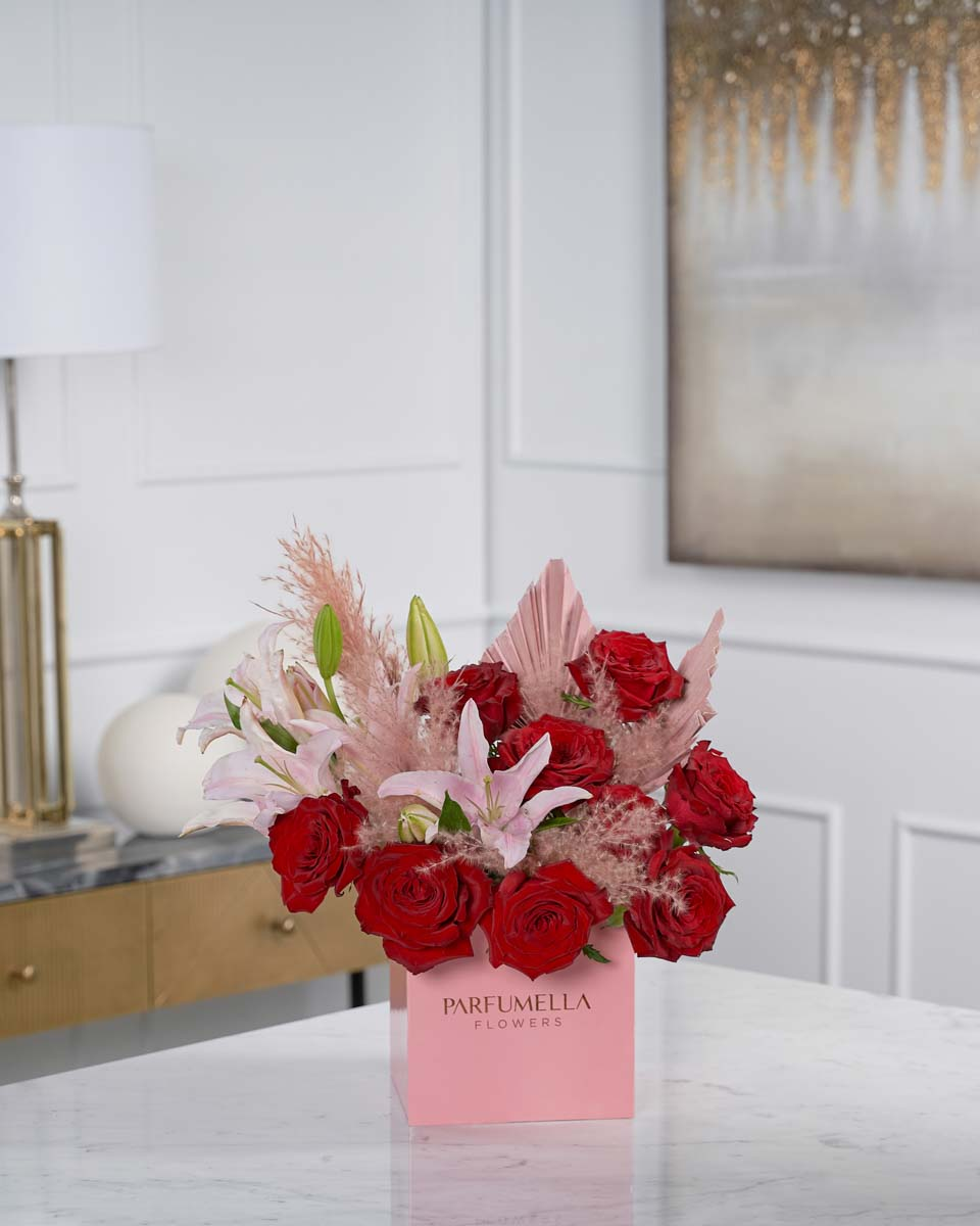 roses, lilies, pampas and dried palm on pink box