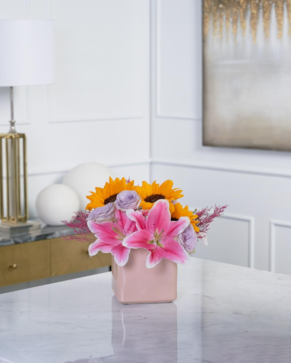 photo of lillies, roses and sunflower on pink vase