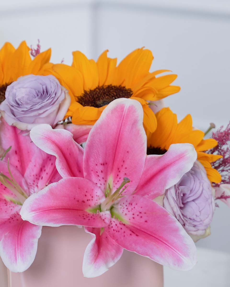 detailed photo of lillies, roses and sunflower on pink vase